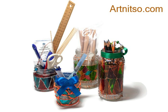 Four used glass jars painted with glass paint in colourful designs. The jars have art and craft supplies held in them and are being used as storage.