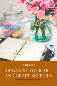 Pinterest image with jars of chalk and flowers and note book. Text says - 12 steps to oragnise your art and craft supplies - read the post at artnitso.com
