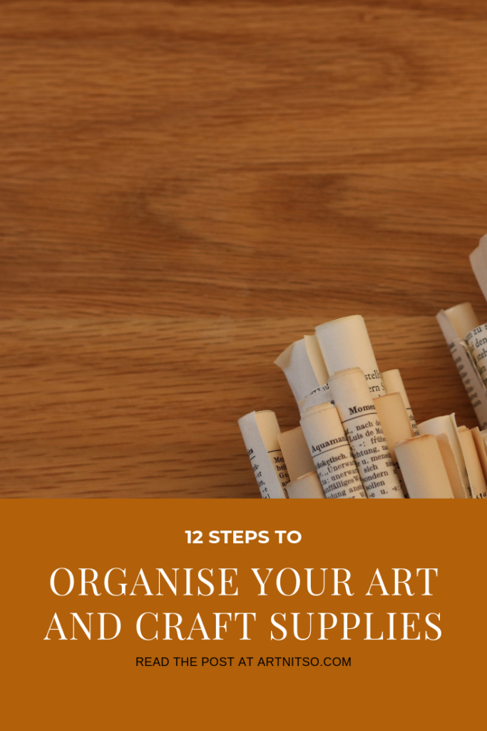 Pinterest image of rolled newspaper on a timber backround - text says 12 steps to organise your art and craft supplies - read the post at Artnitso.com.