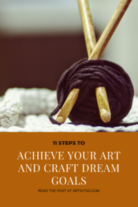 "Pinterest image of 2 knitting needles inserted into purple ball of yarn on white surface with brown background. Text says ""11 steps to achieve your art and craft dream goals. Read the post at Artnitso.com'."