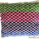Hand knitted pillow in green, fuschia, purple, blue and white in Patons Toto kids yarn. Artnitso.com text.