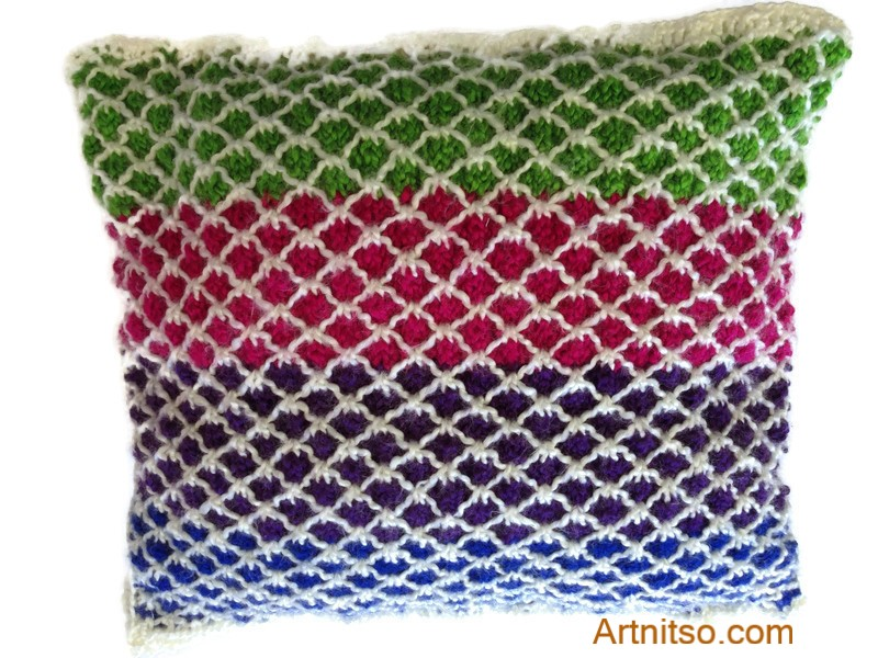 The result of using art and craft to balance emotions. Hand knitted pillow in green, fuschia, purple, blue and white in Patons Toto kids yarn. Artnitso.com text.