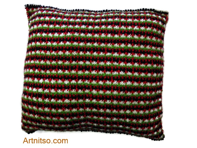 The result of using art and craft to balance emotions. Hand knitted pillow in green, black red, white in Patons Toto Kids yarn. Artnitso.com text.