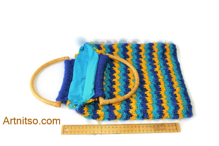 The result of using art and craft to balance emotions. Hand knitted bag with curved cane handles. Knitted in light blue, dark blue and yellow Toto Kids yarn. Lined with blue poly cotton. Artnitso.com text.