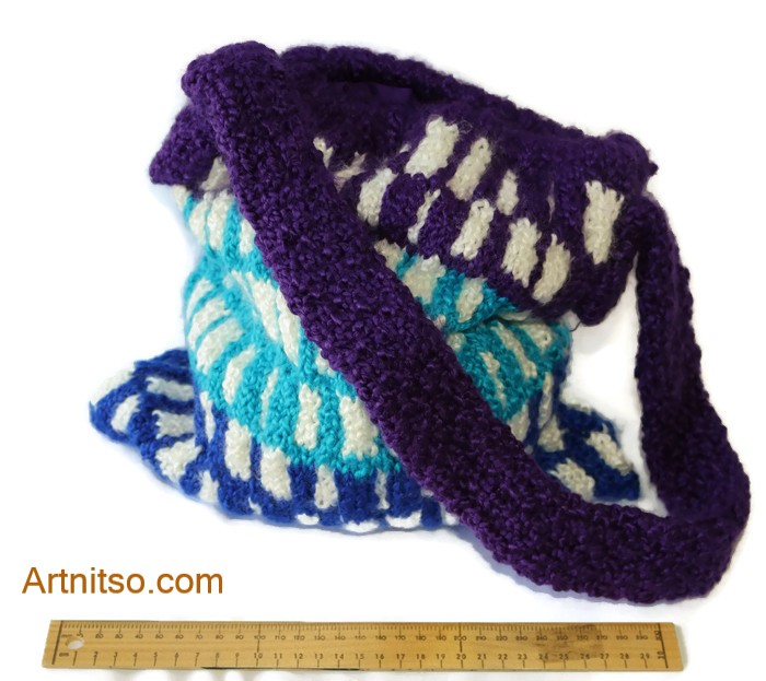 The result of using art and craft to balance emotions. Hand knitted bag with knitted purple handle. Purple, white, light blue and dark blue pattern in Patons Toto Kids yarn. Artnitso.com text.