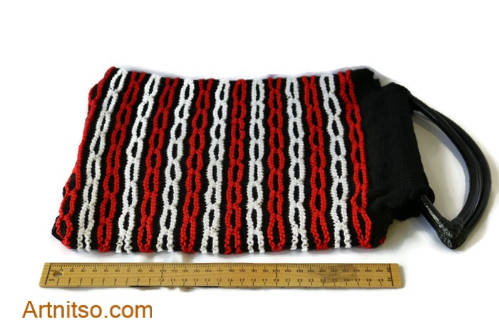 The result of using art and craft to balance emotions. Hand knitted cotton bag with black cane handles. Red, Black and white chain pattern using cotton yarn. Artnitso.com text.