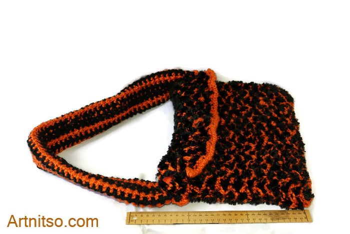 The result of using art and craft to balance emotions. Hand knitted bag using orange and black yarn. Artnitso.com text.