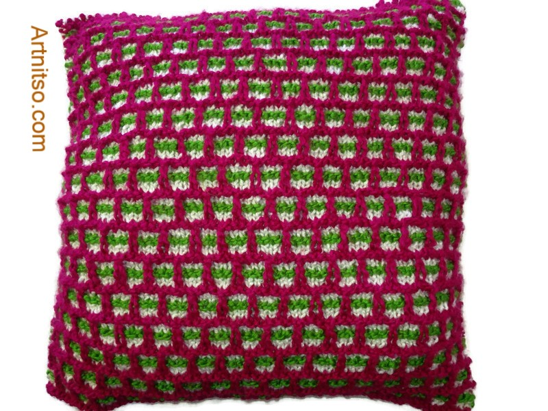 The result of using art and craft to balance emotions. Hand knitted pillow in fuschia, green and white pattern using Patons Toto Kids yarn. Artnitso.com text.