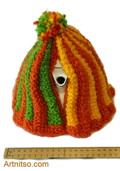 The result of using art and craft to balance emotions. Hand knitted tea cosy using Patons Toto Kids yarn. Green, orange and yellow yarn. Artnitso.com text.