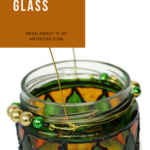Pinterest image of yellow, green, orange and black glass jar. Text says 'Try painting glass. Read about it at Artnitso.com.
