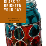 "Pinterest image of silver, red and blue painted glass jar. Text says ""Shake the blues and paint glass to brighten your day. Read about it at Artnitso.com."