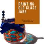 "Pinterest image with painted glass jar and ribbon. Text says ""make your own useful utensils by painting old glass jars. Read about it at artnitso.com."